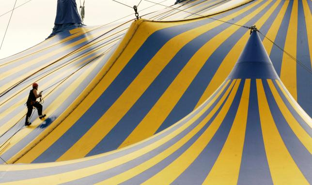 A worker climbs to top of a circus tent in San Francisco in this file photo
