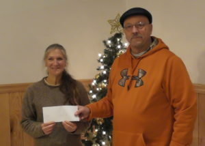 Dave Farringer of the Brookville Fireman's Club presents a check to Margo Stefanic of the Willow Run Animal Sanctuary.