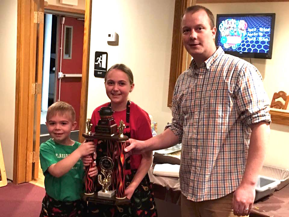 Chad Brooks, right, awards the 2017 Chili Cook-Off trophy to Alyse Smith, center and Gavin Smith.